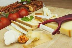 Affettare formaggio, preparante per il ricevimento all'aperto domestico Alimenti a rapida preparazione da wine e birra Canape del Fotografia Stock