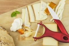 Affettare formaggio, preparante per il ricevimento all'aperto domestico Alimenti a rapida preparazione da wine e birra Canape del Fotografia Stock Libera da Diritti