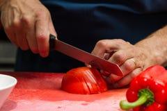 Affettare i pomodori Immagine Stock