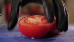 Affettare il pomodoro con il coltello da cucina stock footage
