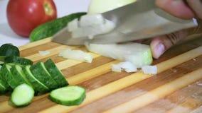 Affettare le cipolle fresche su un tagliere con un grande coltello su un fondo del pomodoro stock footage