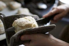Affettare pane caldo con il coltello di pane Fotografie Stock