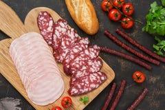Affettare varie salsiccie con i pomodori, le baguette ed il prezzemolo dei peperoncini rossi su un fondo scuro Vista da sopra Immagini Stock