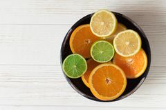 Affettato del limone, dell'arancia e della limetta in ciotola ceramica blu su w bianco Immagini Stock