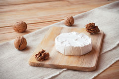 Affettato intorno al formaggio del camembert su un bordo di legno con i dadi Immagini Stock Libere da Diritti