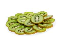 Affettato sulle fette di un piatto di kiwi della frutta tropicale su un fondo bianco fotografia stock libera da diritti