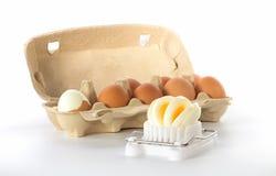 Affettatrice dell'uovo con una scatola di uova immagini stock