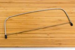 Affettatrice regolabile della taglierina del livellatore del dolce sul tagliere di legno fotografia stock