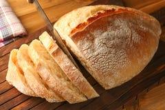Affettatura del pane fresco sul tagliere di legno Fotografia Stock