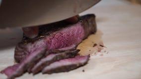 Affettatura della bistecca arrostita su un tagliere archivi video