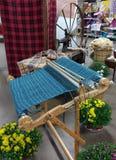 Affichage démodé de textiles comportant un métier à tisser, une machine à coudre de vintage, une roue de rotation antique, et un  Photographie stock