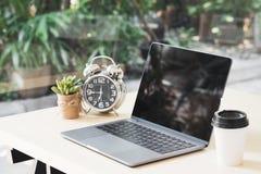 Affichage d'écran noir vide d'ordinateur portable sur la table en bois avec une tasse de Photographie stock