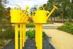 Affichage jaune d'arrosoirs Photos stock