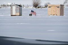 Affichages de drapeau américain entre deux cabanes de pêche de glace près de lac Shoreline images stock