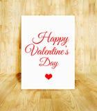 Affiche blanche avec le mot heureux de Saint-Valentin dans le roo en bois de parquet Photographie stock libre de droits