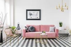 Affiche boven roze bank in woonkamerbinnenland met gouden leunstoel op geruite vloer Echte foto stock foto's