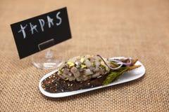 Affiche de TAPAS Tapas espagnols frais et délicieux avec le tartre des harengs et oignons sur une baguette noire Un excellent fon Photographie stock