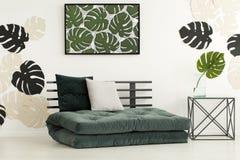 Affiche des feuilles au-dessus du futon avec des coussins dans la chambre à coucher moderne international photographie stock libre de droits
