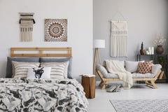Affiche en decor boven gevormd bed in hygge vlak binnenlands met hoofdkussens op houten bank royalty-vrije stock fotografie
