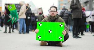 Affiche met het groene scherm in man handen dat op de straat tijdens demonstratie zit stock footage
