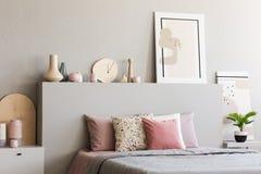 Affiche sur la tête de lit du lit avec les coussins roses dans la chambre à coucher grise dedans photographie stock libre de droits