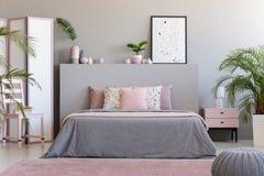 Affiche sur la tête de lit grise dans l'intérieur de chambre à coucher avec les oreillers roses dessus image libre de droits