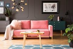 Affiche sur le mur gris dans l'intérieur de salon avec le divan rose et photos libres de droits