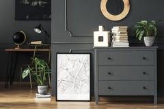 Affiche tussen installatie en grijs kabinet met boeken in huisbureau stock foto