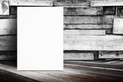 Affiche vide se penchant au mur en bois de planche et au plancher en bois diagonal, images stock