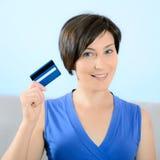 Afficher de sourire de femme par la carte de crédit Image stock
