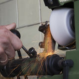 Affilage de pièces en métal, rectifiant dans l'atelier, mains de travailleurs, PS photographie stock libre de droits