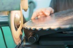 Affilant la circulaire a vu, travailleur affile une lame de scies circulaire Photographie stock libre de droits
