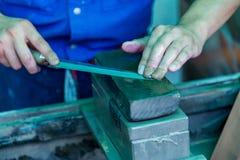 Affilatura del coltello con una pietra per affilare immagini stock