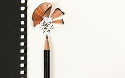 Affilez le crayon sur le bureau blanc Sans compter que le papier noir Photographie stock