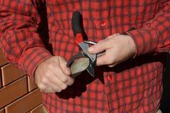 Affilez les cisailles Jardinier Cleaning et affilage des outils de jardin photo stock