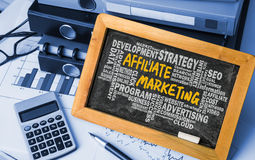 Affiliate marketing handwritten on blackboard with related words Stock Image