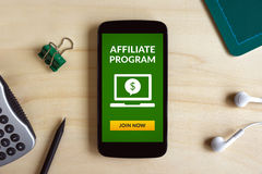 Affiliate program concept on smart phone screen on wooden desk. All screen content is designed by me. Flat lay Royalty Free Stock Image