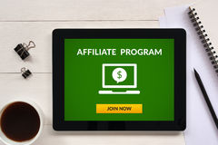 Affiliate program concept on tablet screen with office objects. On white wooden table. All screen content is designed by me. Flat lay Royalty Free Stock Photography