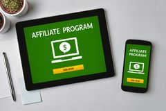 Affiliate program concept on tablet and smartphone screen. Over gray table. All screen content is designed by me. Flat lay Royalty Free Stock Image