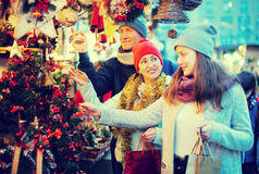 Affirmative family couple with teen girl choosing Christmas deco Stock Photos