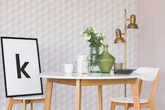 Affisch i svart ram på stol på trätabellen med blommor i exponeringsglasvas i flott matsal som är inre med den geometriska modell arkivbild