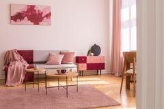 Affisch ovanför den gråa soffan med kuddar i ljus vardagsrum som är inre med tabellen på rosa matta Verkligt foto fotografering för bildbyråer