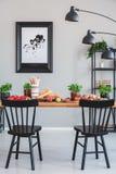 Affisch på den gråa väggen i industriell matsal som är inre med svarta stolar och lampan på tabellen royaltyfria bilder