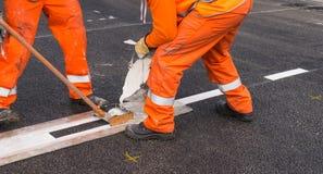 Affixing line marking. Close-up affixing line marking  on the asphalt road surface Royalty Free Stock Images