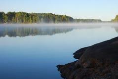 Affleurement rocheux attendant sur le lever de soleil au lac Images libres de droits