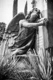 The afflicted angel kneeling on the tomb turns his gaze to the s Stock Photos