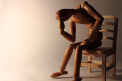Affliction. Worried wooden dummy sitting with copy space Stock Image