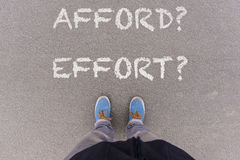 Afford or Effort text on asphalt ground, feet and shoes on floor. Personal perspective footsie concept Royalty Free Stock Photo
