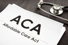 Affordable Care Act ACA and stethoscope on a desk. Affordable Care Act ACA and stethoscope on a wooden desk stock photo