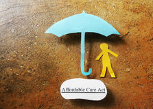 Affordable Care Act health insurance coverage. Paper person under Affordable Care Act umbrella - Obamacare concept royalty free stock images